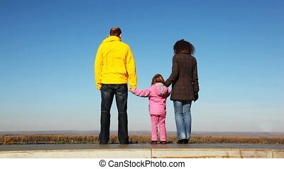 family of mum, daddies and daughter goes upwards from platform before survey kind of wood and sky
