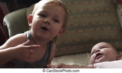 Little blonde boy play with baby lie on sofa. Children. Love. Brother. Sister.