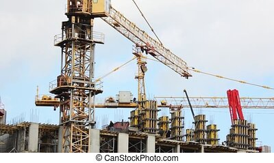 elevating crane moves blocks on building site of under construction house