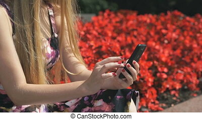 Young girl holds a cellphone and reads messages