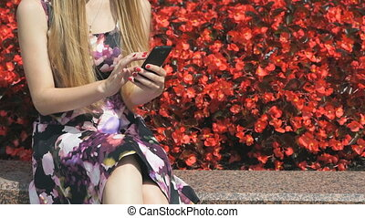 Girl holding a smartphone in the park outdoors