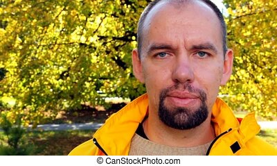 mans face in yellow jacket close up in park in autumn