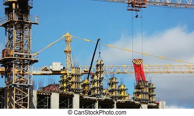elevating crane lifts and moves blocks on building site of...