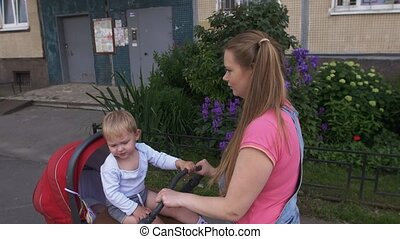 Young mother walk with baby carriage Family Little son sit...