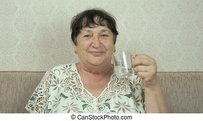 Elderly woman smiles, drinks water, shows thumb up