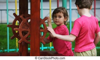 boy and girl in crimson vests twist handles of an artificial well