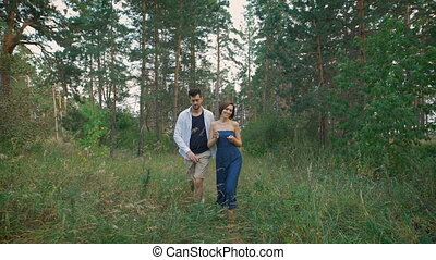 Young couple walking in the woods or the park, not far from his home.