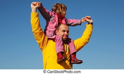 portrait of daughter sits at daddy on shoulders against clear sky
