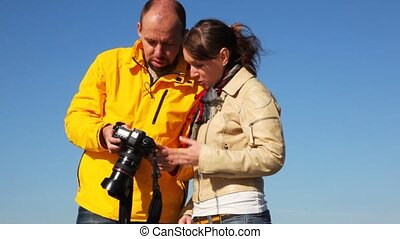 man and woman takes photocamera in hands, look an it, talk and smile against clear sky