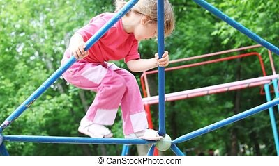 little girl blonde in pink clothes climbs on iron rod on children\'s playground