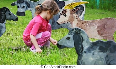 girl on lawn feeds with grass drawn silhouette of nanny-goat