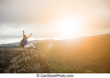 backpacker woman relaxing and victory hand rising on rock...