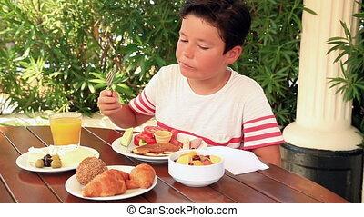 Child eating breakfast at the garden