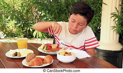 Child eating breakfast at the garden