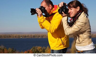 man and woman takes photocamera in hands and photograph something on nature against the river, wood and an clear sky