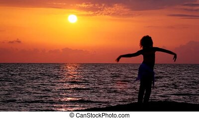 silhouette of young woman dancing on beach, sunset sky and sea in background