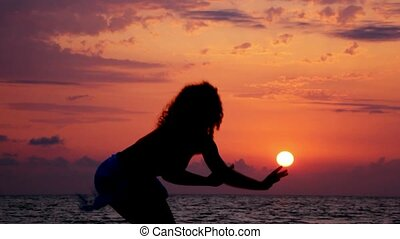 silhouette of young dancing woman on beach, sunset sea and sky in background