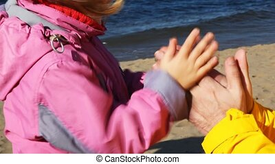 daughter and father play, clap together in palms on...