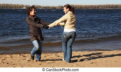 two women are turned keeping for hands and smile on river...