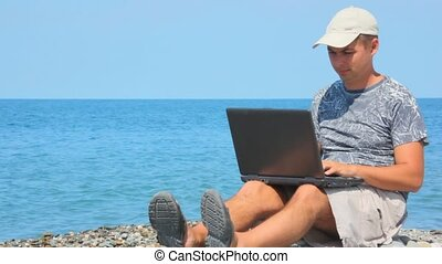 man with notebook sitting on rocky beach, sea in background