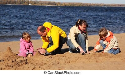 family of mother, father, son and daughter build hills of sand on river beach