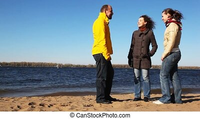 man and two woman stands on coastline of river talk and smile