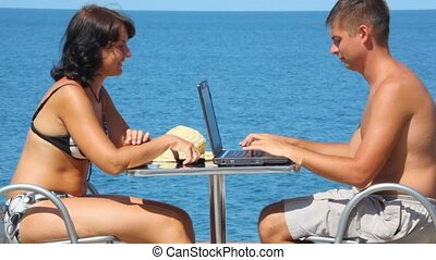 woman with cell phone and man using notebook sits at table, sea in background