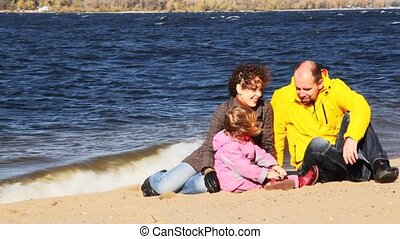 family of mum, daddies and daughter sits on sandy to river...