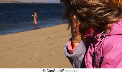 girl sits on beach and looks at woman who bathes in river -...