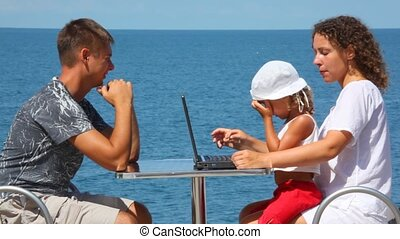 happy family of three persons with notebook sits at table, sea in background