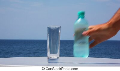 pouring water from bottle into glass, sea and sky in...