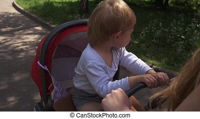 Mother ride baby carriage Motherhood Little son sitting on...