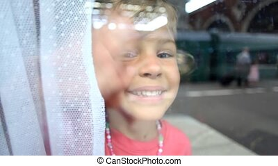 little girl looking, smiling and waving from the train window