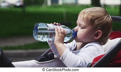 Little boy drink water from bottle in baby carriage on...