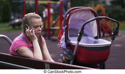 Young mother speak to phone on playground. Red baby...