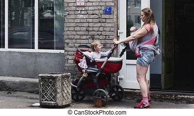 Mother with baby on sling take baby carriage with son. Give...