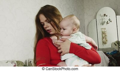 Mother in red shirt hold little baby on hands. Motherhood. Healthcare. Love