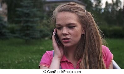 Young attractive girl with freckles speak to phone on bench...