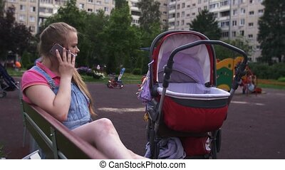 Young mother speak to phone on playground. Red baby carriage. Kids. Summer