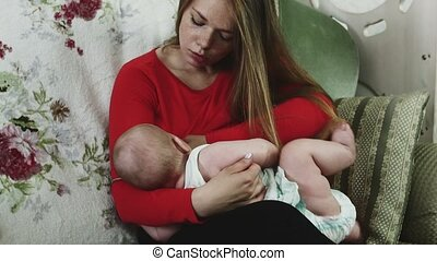 Mother in red shirt breastfeeding little baby on sofa. Motherhood. Immunity.