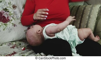 Young mother in red shirt breastfeeding little baby on sofa. Motherhood.