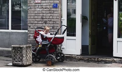 Little boy play with toy in baby carriage on street. Mother walk out with baby.
