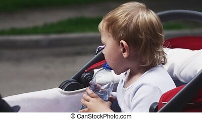 Little blonde boy drink water from bottle in baby carriage. Summer day. Child