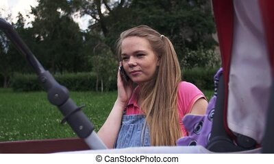 Young mother speak to phone on bench Baby carriage Summer...