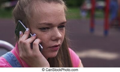 Young attractive girl with freckles speak to phone on...