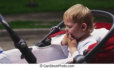 Little blonde boy eating kinder surprise in baby carriage on...