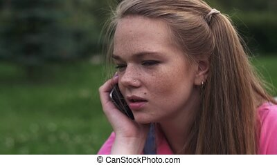 Young attractive girl with freckles speak to phone Summer...