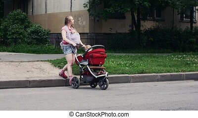 Young mother with baby in sling ride baby carriage with son...