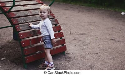 Little boy playing on children slide on playground in summer park. Childhood