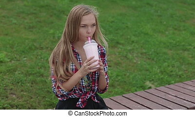 Young woman drinking a healthy smoothie in the street...
